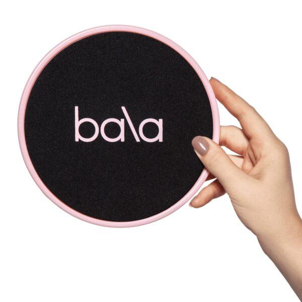 Bala slider i hånd. Svart forside med rosa logo og kant